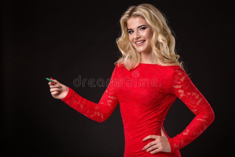 Ung härlig blond kvinna med pokerchiper över svart poker royaltyfri bild