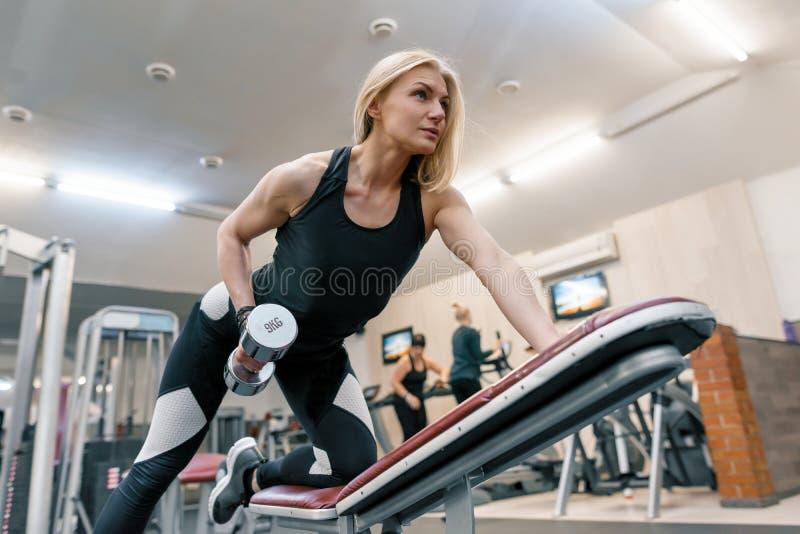 Ung härlig blond kvinna som gör styrkaövningar med hantlar i idrottshall Sport kondition, bodybuilding, utbildning, genomkörare royaltyfri fotografi