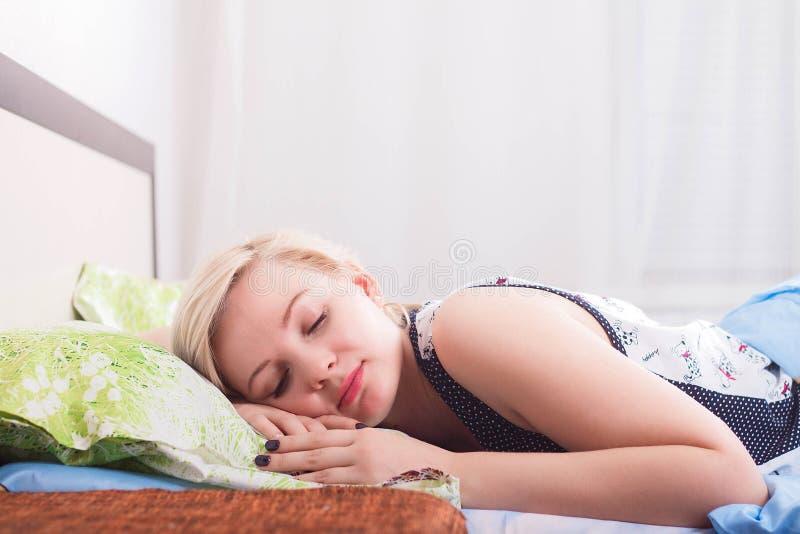 Ung härlig blond kvinna som sover i hennes säng i morgonen fotografering för bildbyråer