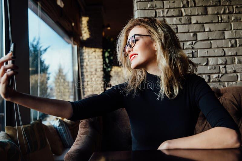 Ung härlig blond kvinna som tar en selfie i coffee shop Hipster röda kanter, exponeringsglas arkivbild