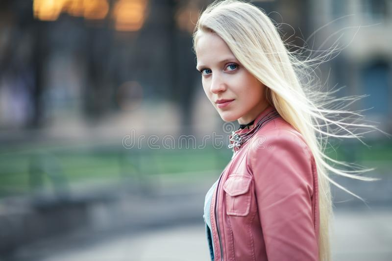 Ung härlig blond kvinnastående som poserar i stadsgata på su royaltyfri foto
