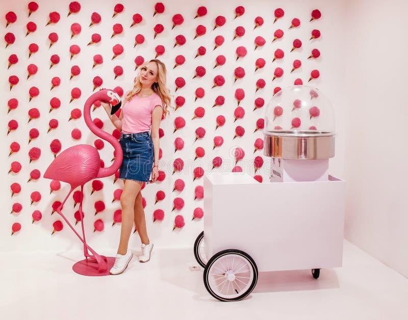Ung härlig blondieflicka som poserar mot en väggbakgrund med rosa glass och utrustning för framställning av söt bomull Swee royaltyfria bilder
