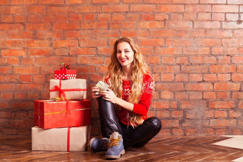 Ung härlig blondin flickan i en röd tröja med med många royaltyfri bild