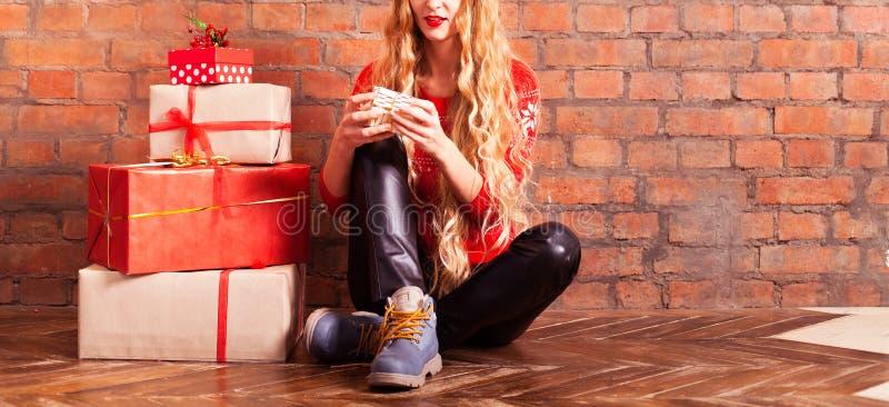 Ung härlig blondin flickan i en röd tröja med med många royaltyfria foton