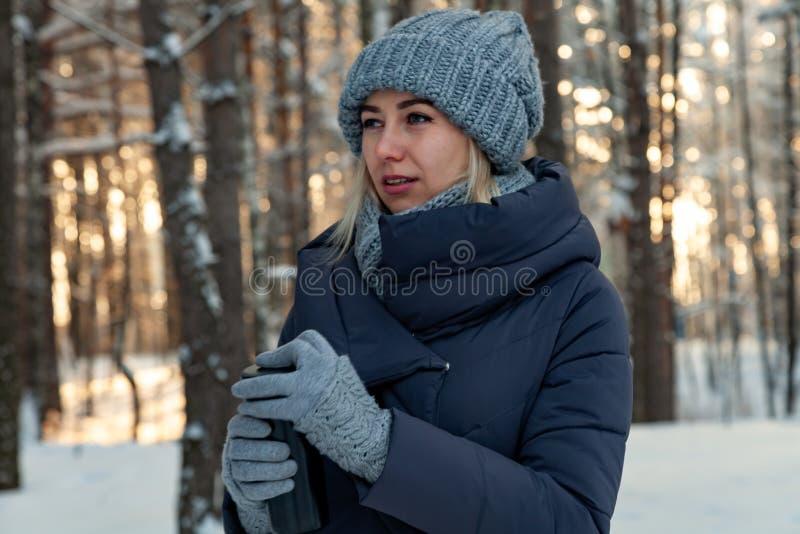 Ung härlig blondin i drinkar kaffe eller te för en stucken hatt, halsduk- och handskei den vinter snö-täckte skogen på solnedgång arkivfoto