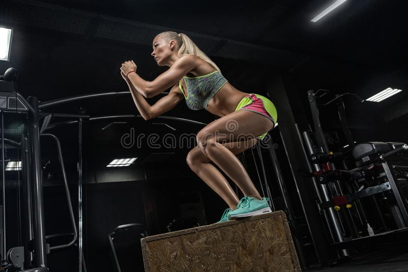 Ung härlig bodybuildingflicka som gör övningar i en modern gy royaltyfri bild