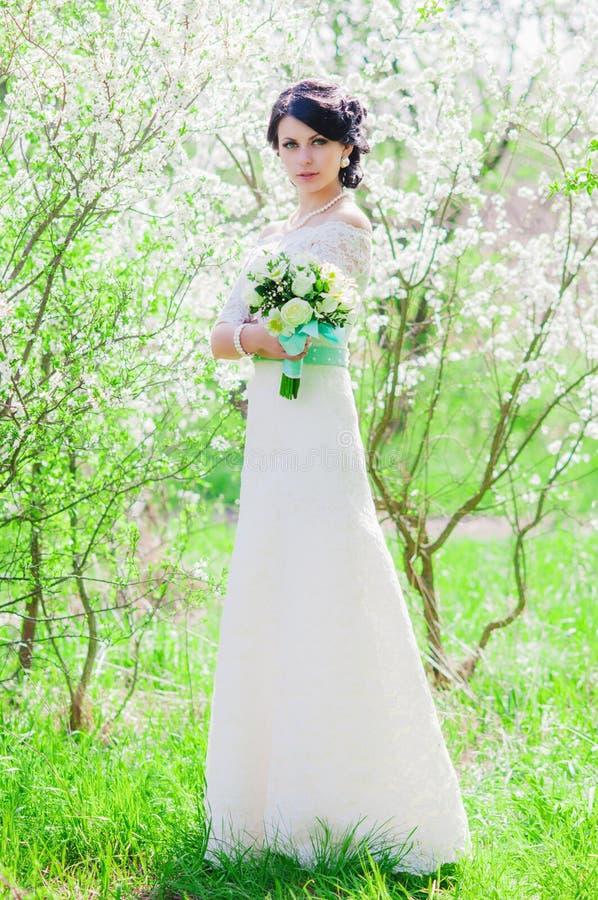 Ung härlig brud i en blomstra trädgård i vår arkivbild