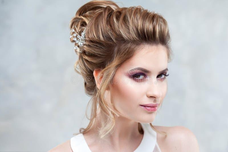 Ung härlig brud med en elegant hög frisyr Bröllopfrisyr med tillbehören i hennes hår royaltyfri foto