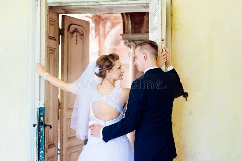 Ung härlig brud och brudgum nära gammal dörr royaltyfria foton