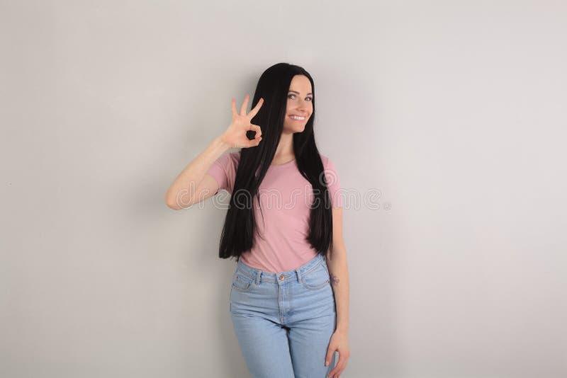Ung härlig brunettkvinna med långt hår som står vid den bärande jeansen för grå bakgrund och den rosa skjortan som ler och arkivbild