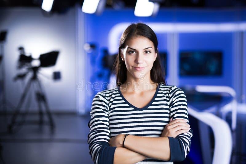 Ung härlig brunetttelevisionhallåman på studioanseendet bredvid kameran TVdirektör på redaktören i studio arkivbilder