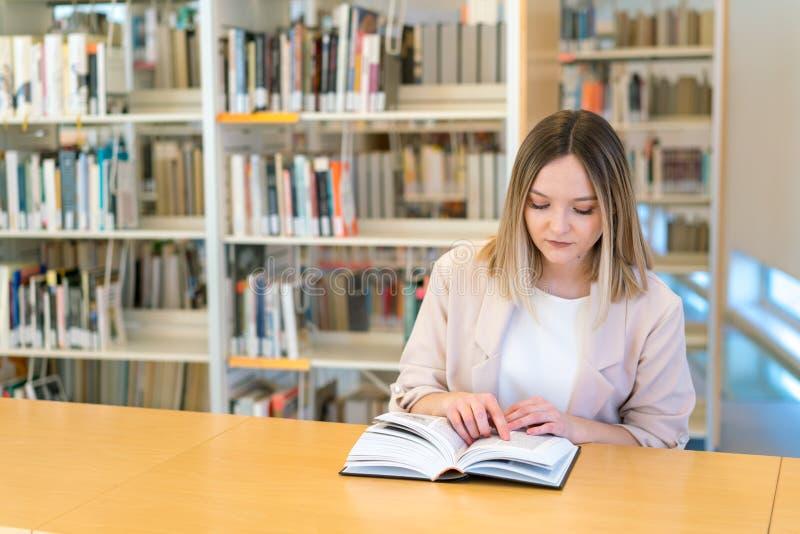 Ung härlig caucasian flicka som läser en bok i arkivet som pekar med hennes finger royaltyfria bilder