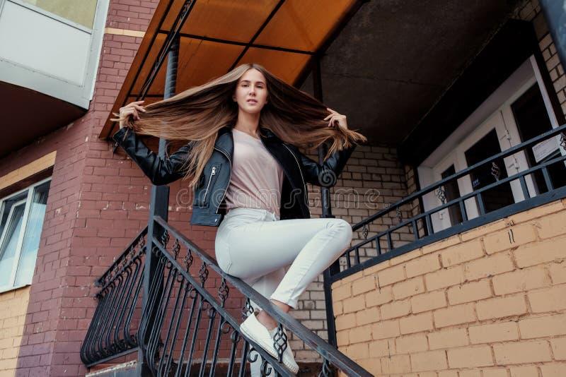 Ung härlig caucasian flicka som poserar i ett svartläderomslag på en bakgrund för tegelstenvägg arkivbild