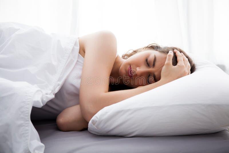 Ung härlig Caucasian kvinna på säng som har huvudvärk/sömnlöshet/migrän/spänning royaltyfri foto