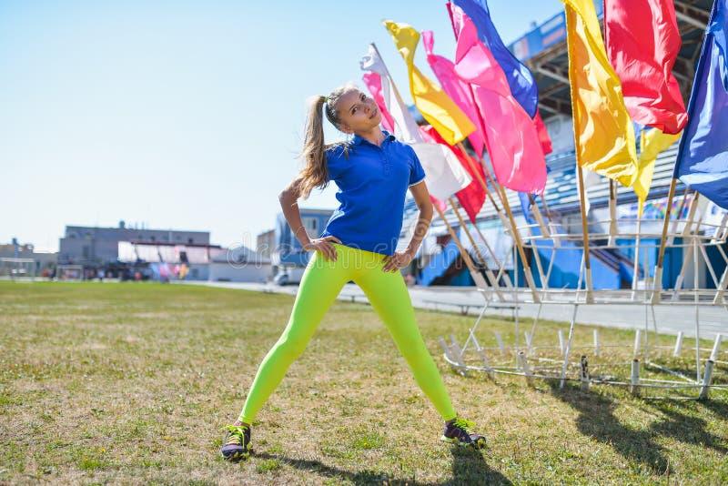 Ung härlig caucasian kvinna som gör konditiongenomkörare på grönt gräs på stadion royaltyfria bilder