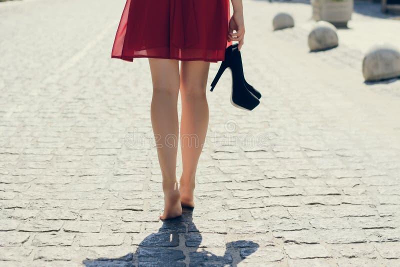 Ung härlig dam i röd klänning, med svarta hög-häl i hand arkivfoto