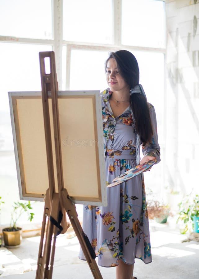 Ung härlig dammålare i klänningen, kvinnakonstnärmålning royaltyfria bilder