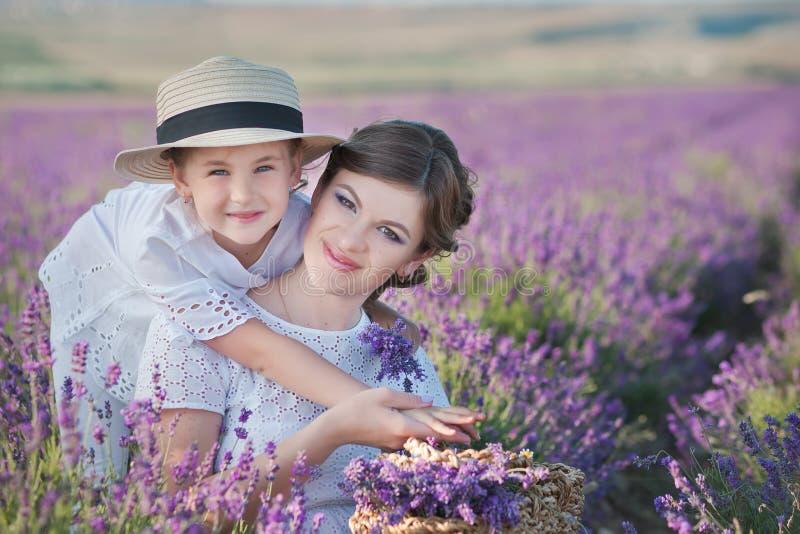 Ung härlig dammoder med den älskvärda dottern som går på lavendelfältet på en helgdag i underbara klänningar och hattar royaltyfria foton