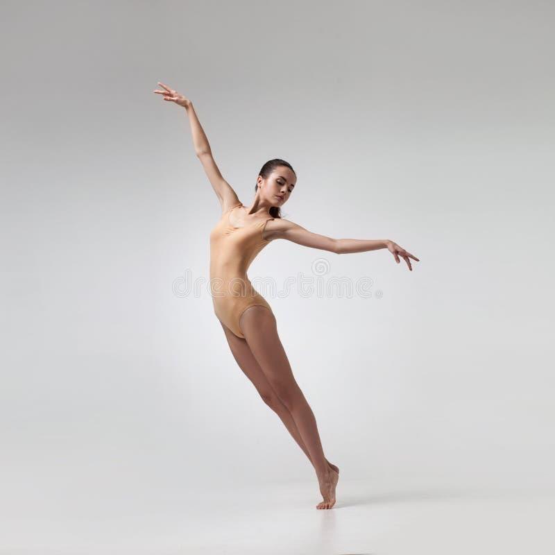 Ung härlig dansare i beige baddräkt arkivfoton