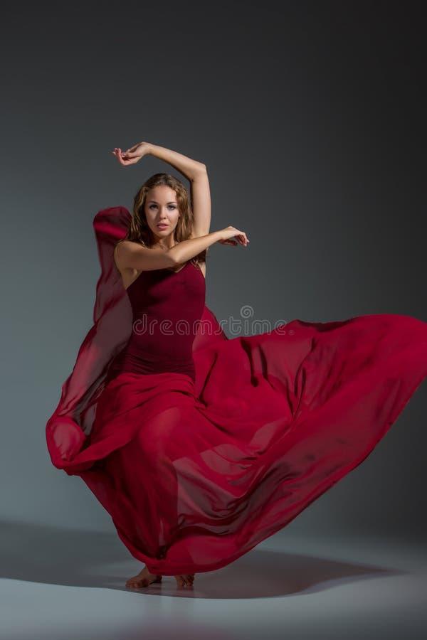 Ung härlig dansare i den röda klänningen som poserar på ett mörker - grå studiobakgrund royaltyfria bilder