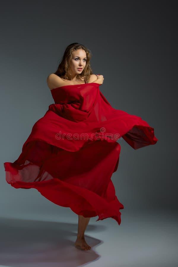 Ung härlig dansare i den röda klänningen som poserar på ett mörker - grå studiobakgrund royaltyfri fotografi