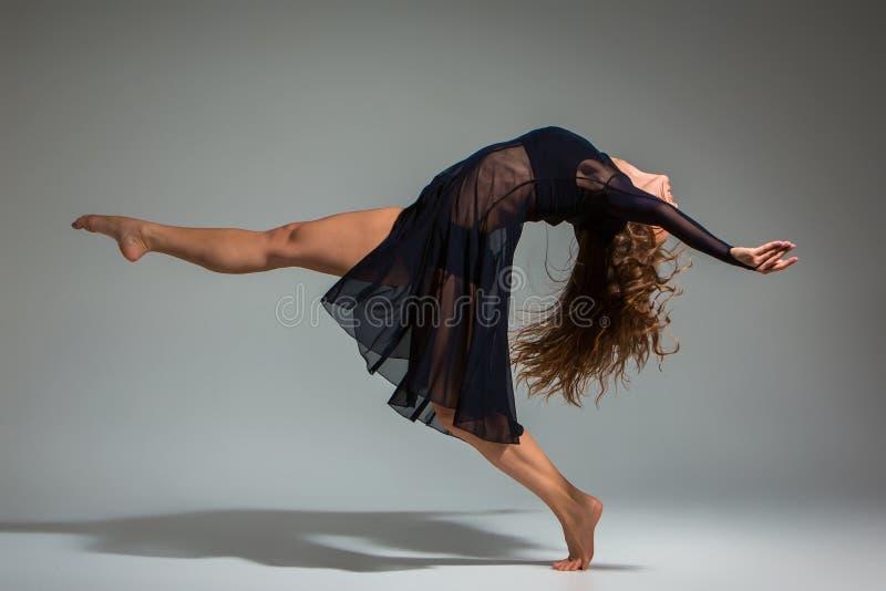 Ung härlig dansare i den svarta klänningen som poserar på ett mörker - grå studiobakgrund arkivbilder