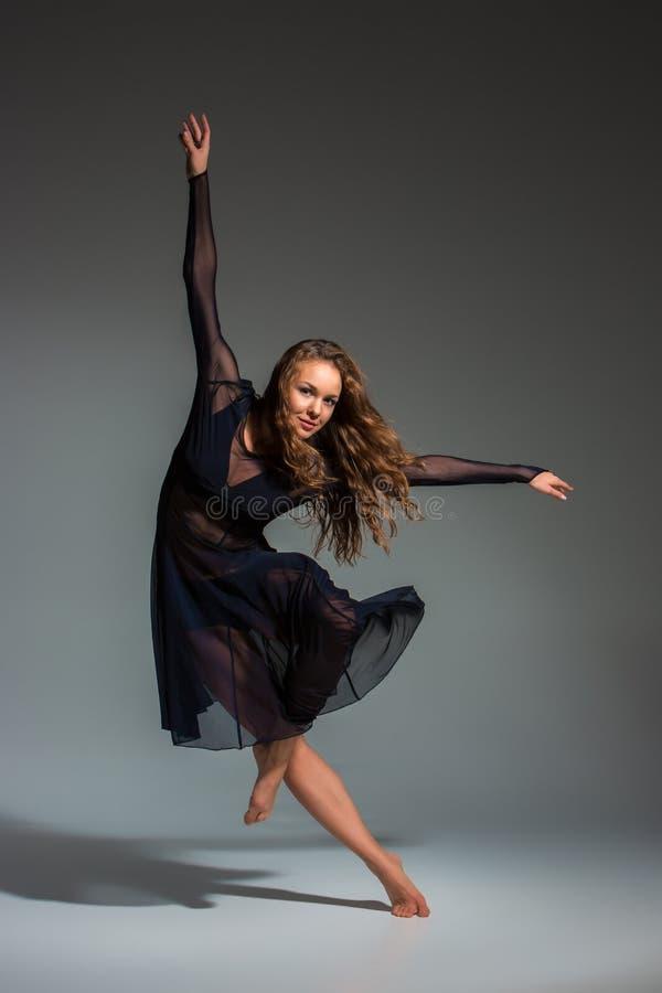 Ung härlig dansare i den svarta klänningen som poserar på ett mörker - grå studiobakgrund royaltyfri bild