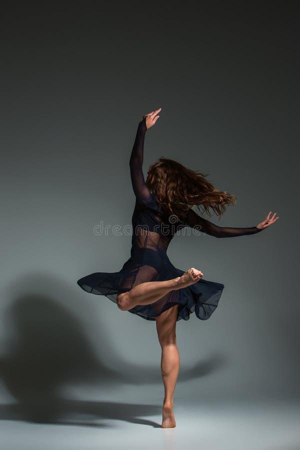 Ung härlig dansare i den svarta klänningen som poserar på ett mörker - grå studiobakgrund royaltyfria foton