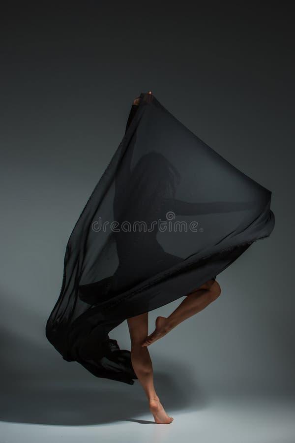 Ung härlig dansare i den svarta klänningen som poserar på ett mörker - grå studiobakgrund royaltyfri foto