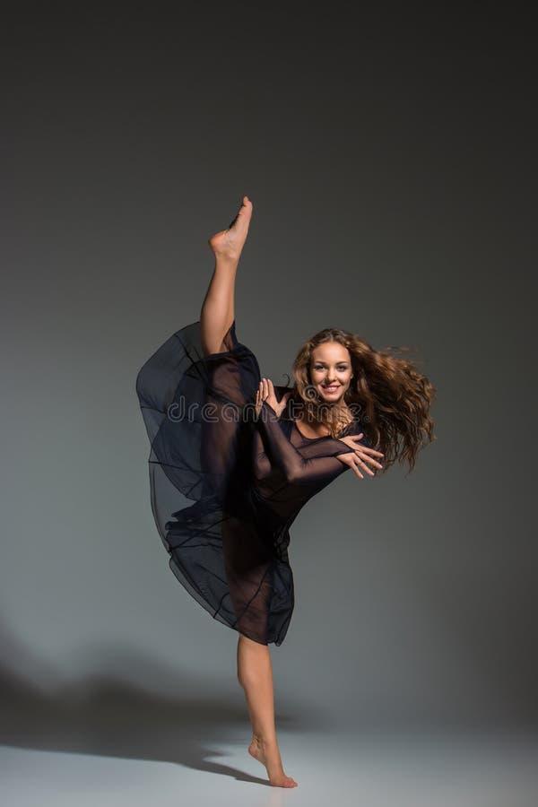 Ung härlig dansare i den svarta klänningen som poserar på ett mörker - grå studiobakgrund fotografering för bildbyråer