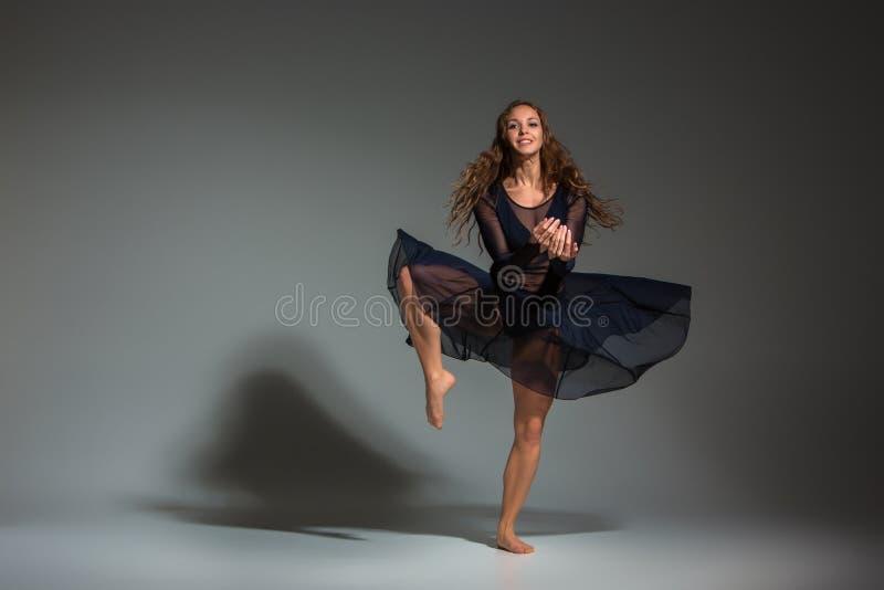 Ung härlig dansare i den svarta klänningen som poserar på ett mörker - grå studiobakgrund royaltyfria bilder
