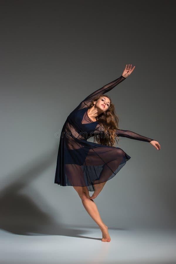 Ung härlig dansare i den svarta klänningen som poserar på ett mörker - grå studiobakgrund arkivfoton