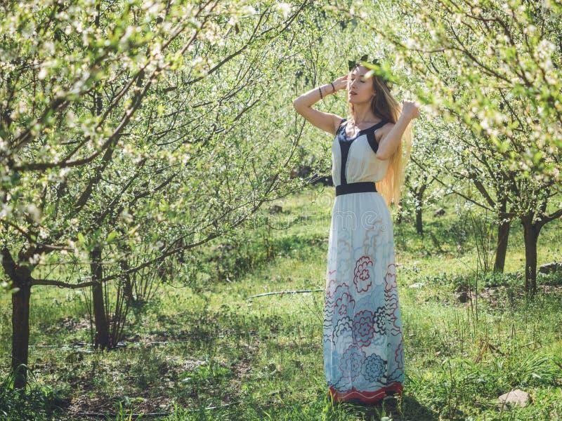 Ung härlig drömma kvinna i vårblomningträd royaltyfria bilder
