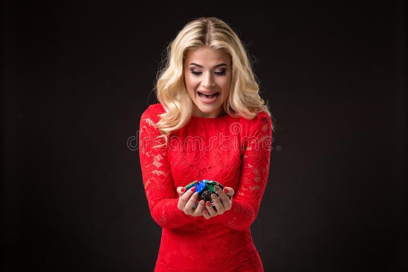 Ung härlig emotionell kvinna med chiper i händer på en svart bakgrund i studion poker arkivbild