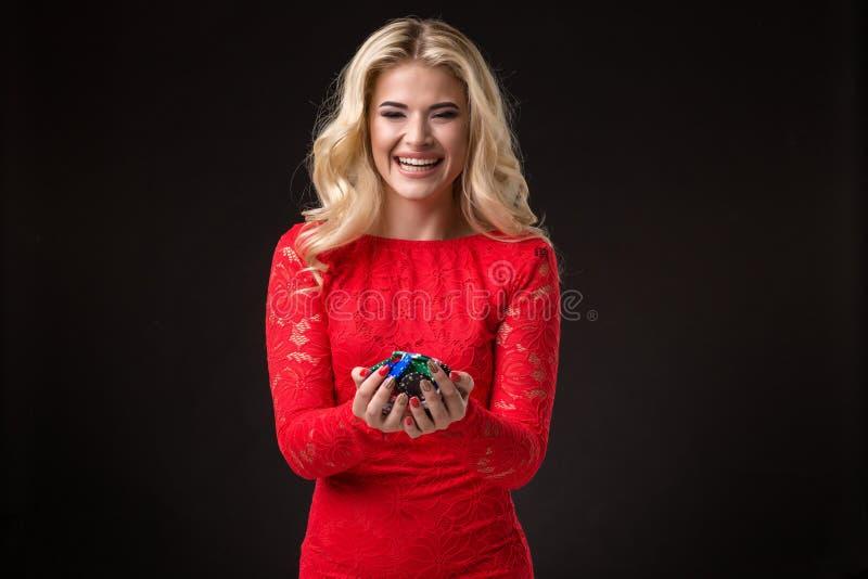 Ung härlig emotionell kvinna med chiper i händer på en svart bakgrund i studion poker arkivfoto