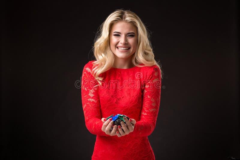 Ung härlig emotionell kvinna med chiper i händer på en svart bakgrund i studion poker royaltyfri foto