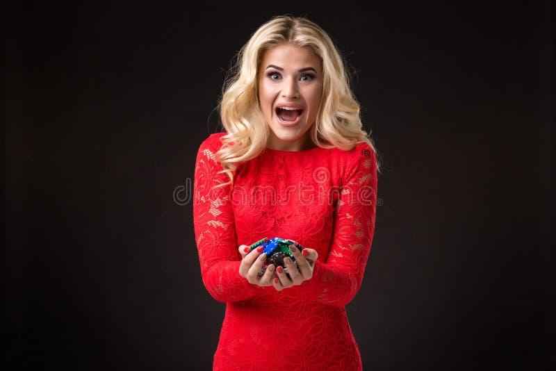 Ung härlig emotionell kvinna med chiper i händer på en svart bakgrund i studion poker royaltyfria foton