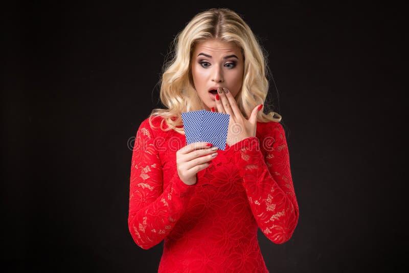 Ung härlig emotionell kvinna med kort i händer på en svart bakgrund i studion poker royaltyfri foto