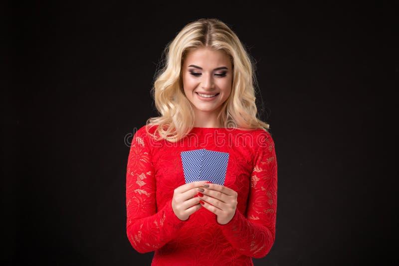 Ung härlig emotionell kvinna med kort i händer på en svart bakgrund i studion poker arkivbild