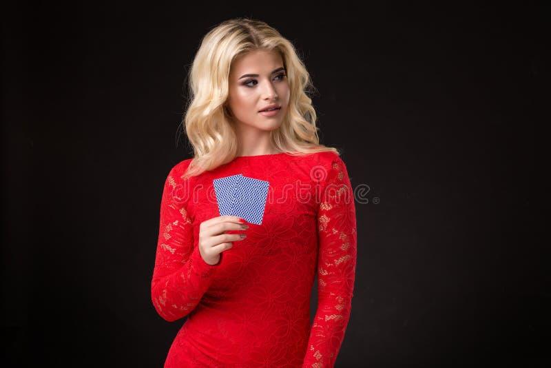 Ung härlig emotionell kvinna med kort i händer på en svart bakgrund i studion poker arkivbilder