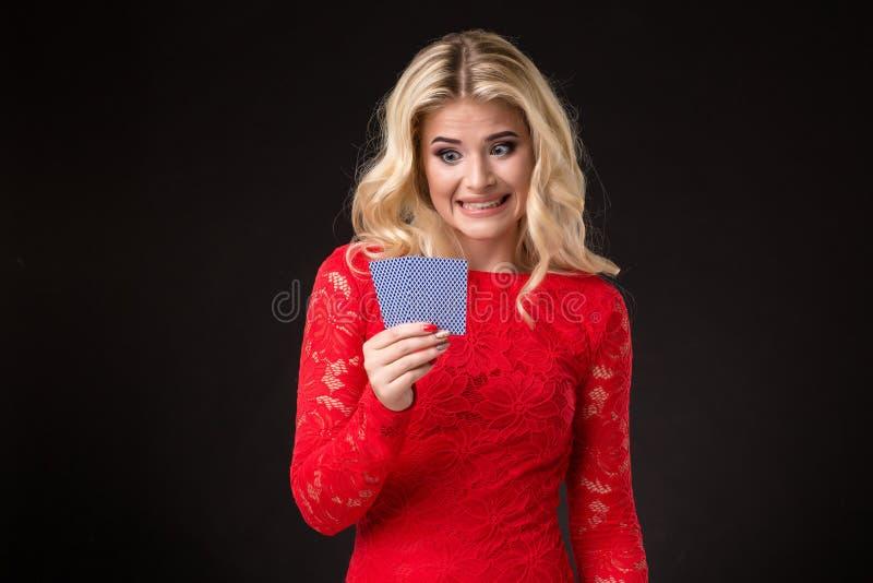 Ung härlig emotionell kvinna med kort i händer på en svart bakgrund i studion poker royaltyfria bilder