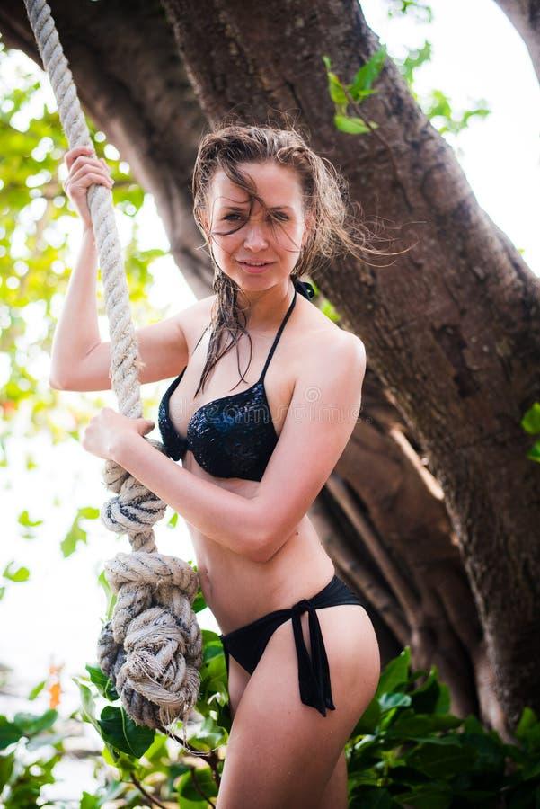 Ung härlig flicka i bikini som går i tropisk skog arkivfoto