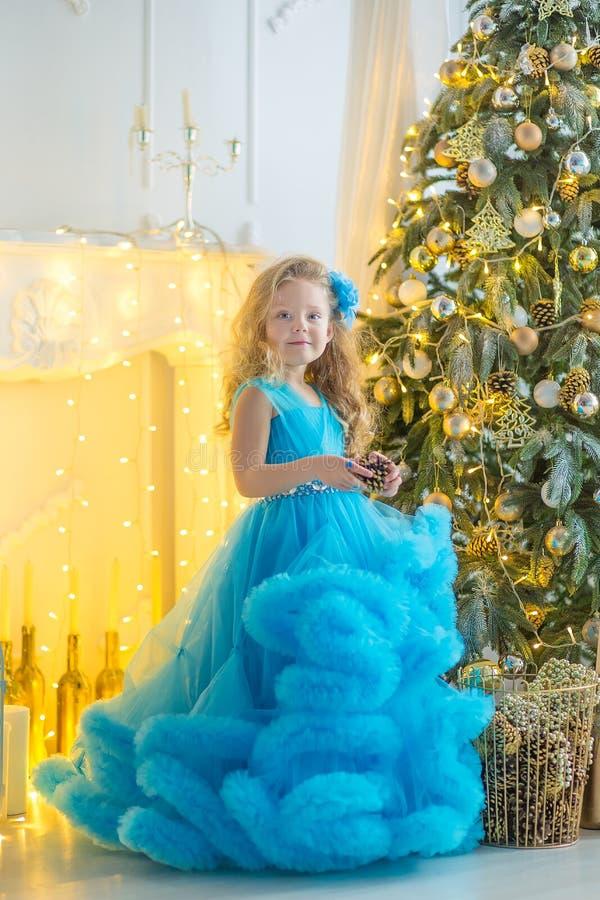 Ung härlig flicka i blått vitt elegant sammanträde för aftonklänning på golv nära julträd och gåvor på ett nytt år royaltyfria foton
