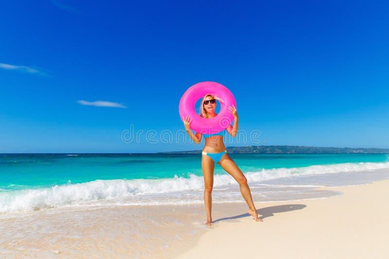 Ung härlig flicka i den blåa bikinin som har gyckel på en tropisk bea arkivbilder