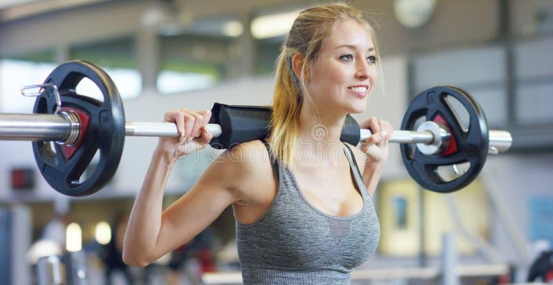 Ung härlig flicka i idrottshallen som gör övningar på det satt med en skivstång som förbättrar musklerna av bakdelarna och benen  royaltyfri fotografi