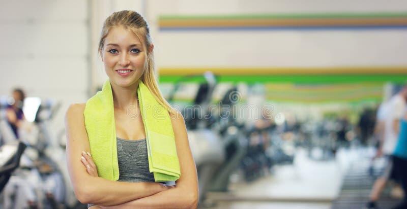 Ung härlig flicka i idrottshallen, ställningar som ler med en handduk på hennes kopplade av skuldra efter coachningen och Begrepp arkivfoton