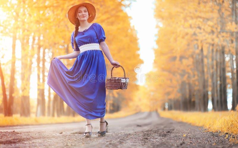 Ung härlig flicka i klänningar på naturen En flicka i en hatt går arkivfoton