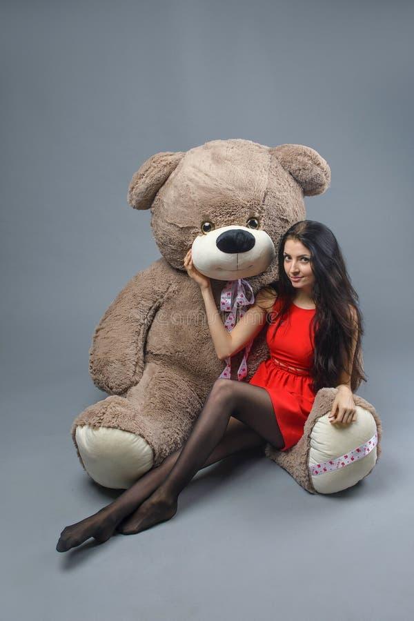 Ung härlig flicka i röd klänning med lyckligt le för stor leksak för nallebjörn mjuk och att spela på grå bakgrund arkivbild