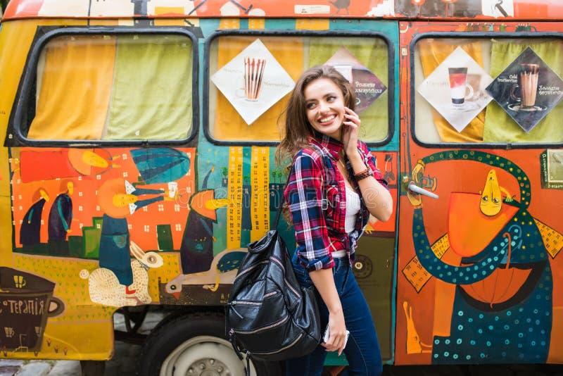 Ung härlig flicka i stilfull kläder framme av den gamla brutna bussen som poserar i stadsgata royaltyfria bilder