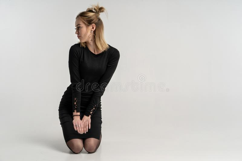 Ung härlig flicka i studio som knäfaller på grå bakgrund fotografering för bildbyråer